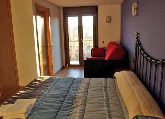 habitación de la casa rural con sofá y cama de matrimonio.