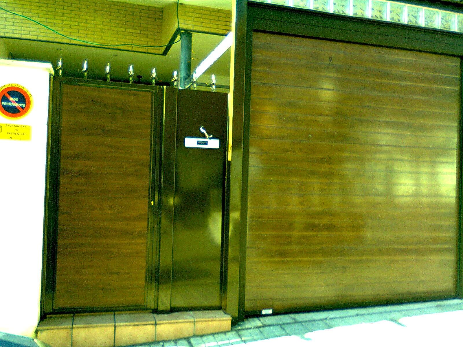 Puerta seccional imitacion madera con puerta peatonal panelada