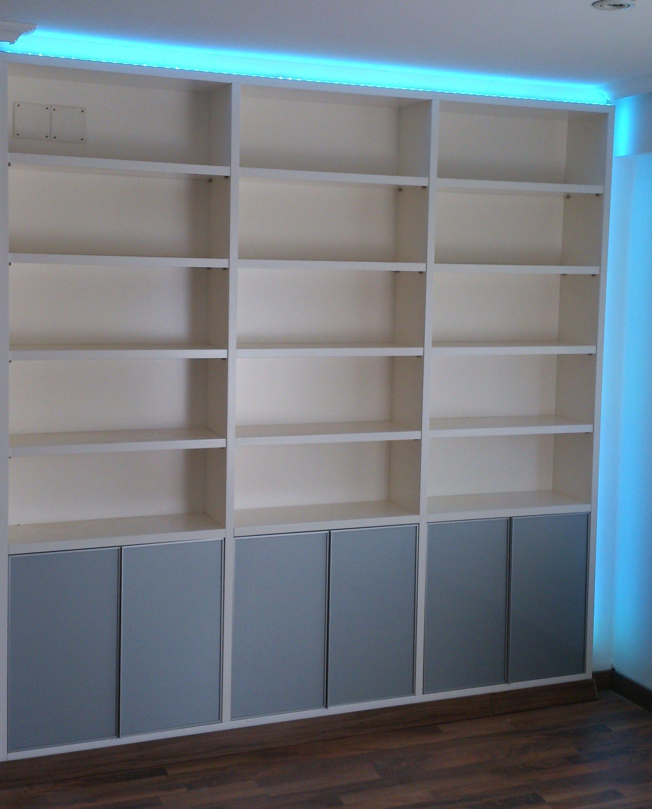 Libreria lacada en Blanco Roto, con puertas inferiores cristal Lacobel Acero y luz indirecta con Leeds RGB de colores
