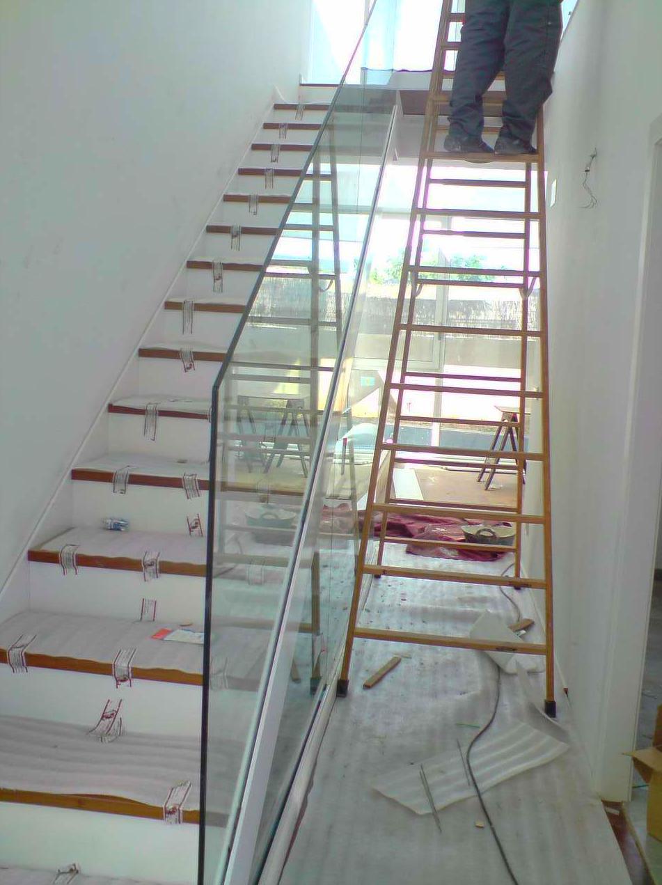 Escalera con peldaños de madera y pasamano de cristal