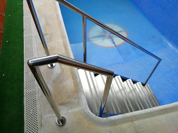 Escaleras con barandilla de acceso a piscina diseñada y fabricada a medida con acero inoxidable calidad AISI 316.