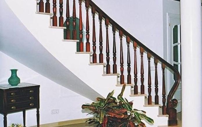 Barandilla curvada sobre mármol en madera de nogal