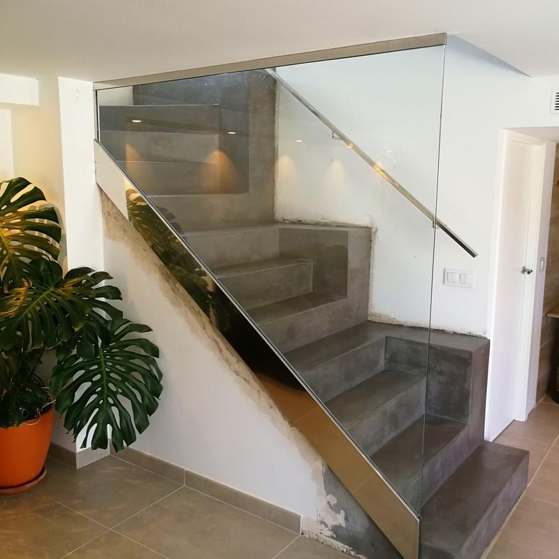 Barandilla de acero inoxidable y vidrio con pasamanos de acero inoxidable diseñada y fabricada a medida para vivienda particular.