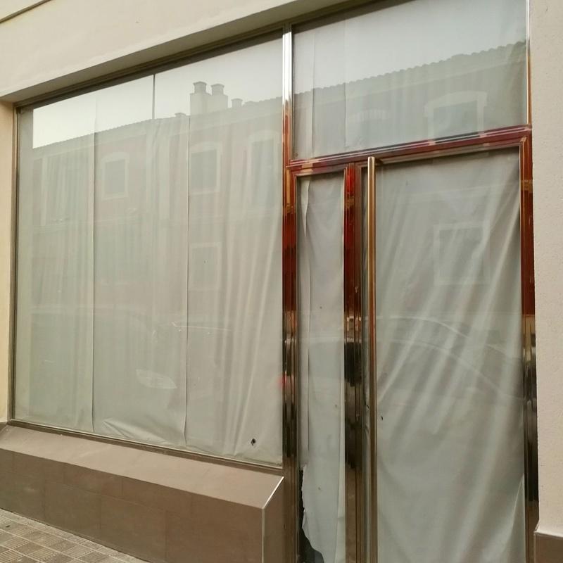 Puerta y escaparate de acero inoxidable y vidrio diseñada y fabricada a medida para local comercial.