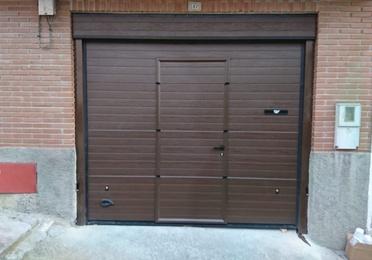 Puerta seccional con puerta de servicio, motorizada