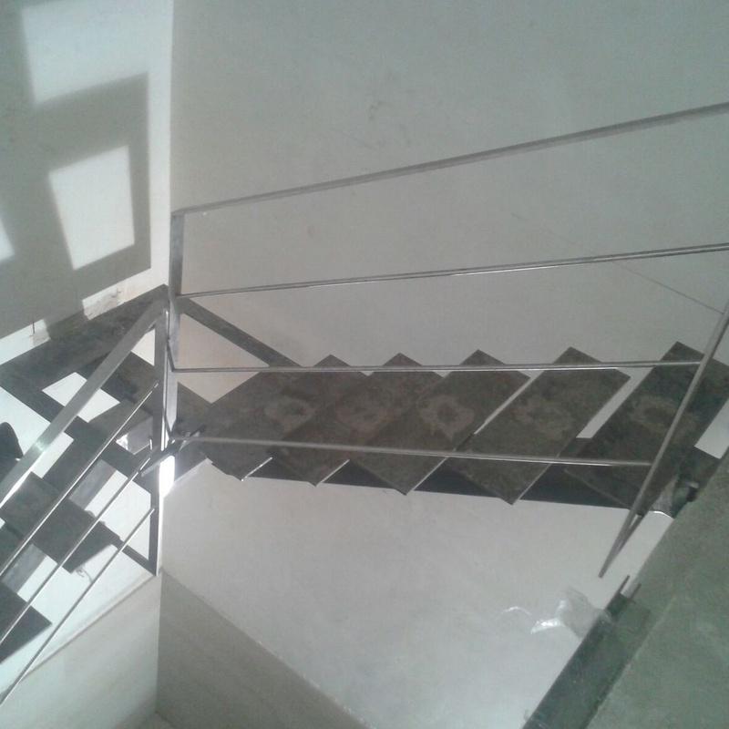 Estructura de escalera preparada para peldaños de madera, con barandilla de inoxidable.