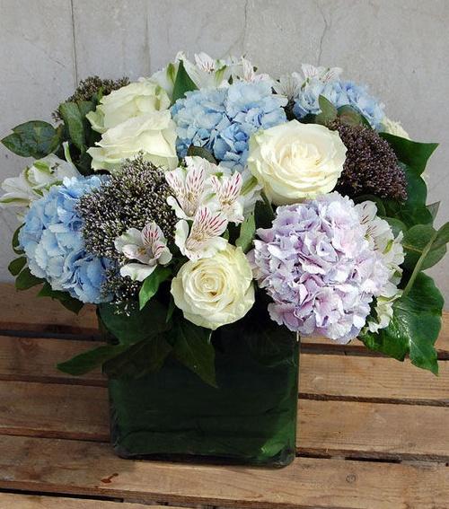 Centro de flores en tonos fríos con hortensia, rosa, alstroemerio, trachelum.