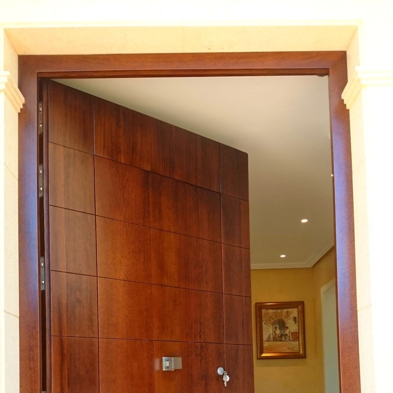 Puerta principal en madera de iroco, apertura total.