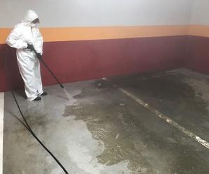 Limpiando un garage, hidrolavadora con agua a alta temperatura.
