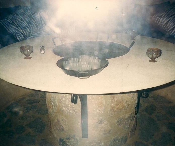 Mesa en piedra natural con barbacoa central