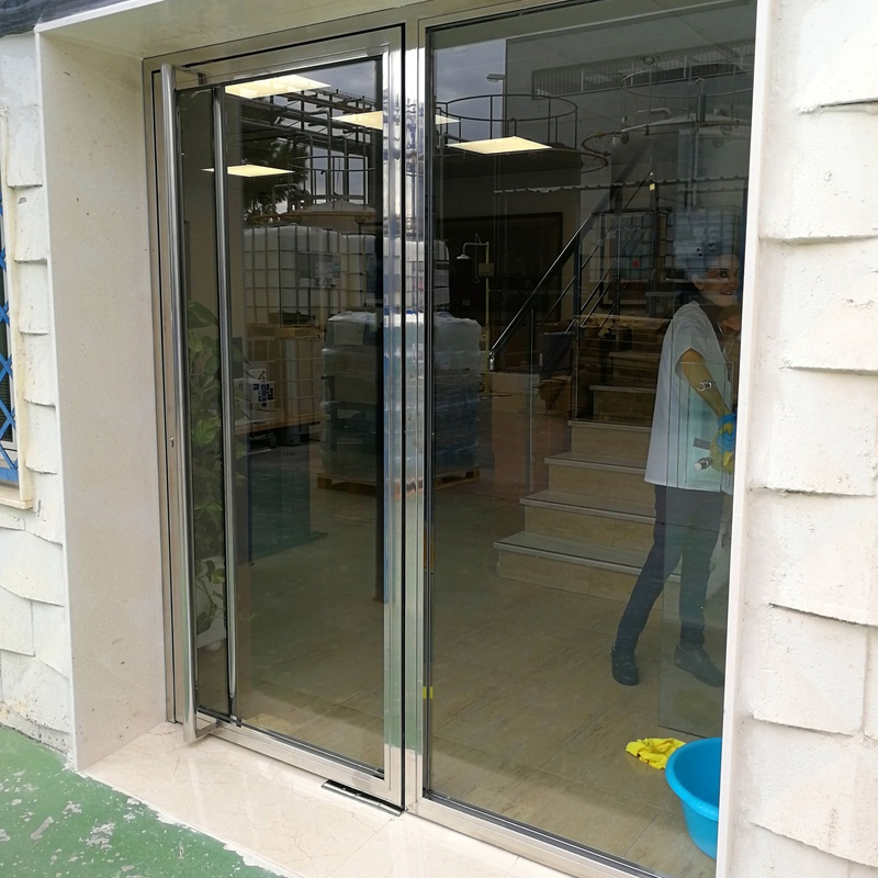 Puerta de acero inoxidable y vidrio diseñada y fabricada a medida para edificio empresarial de zona industrial