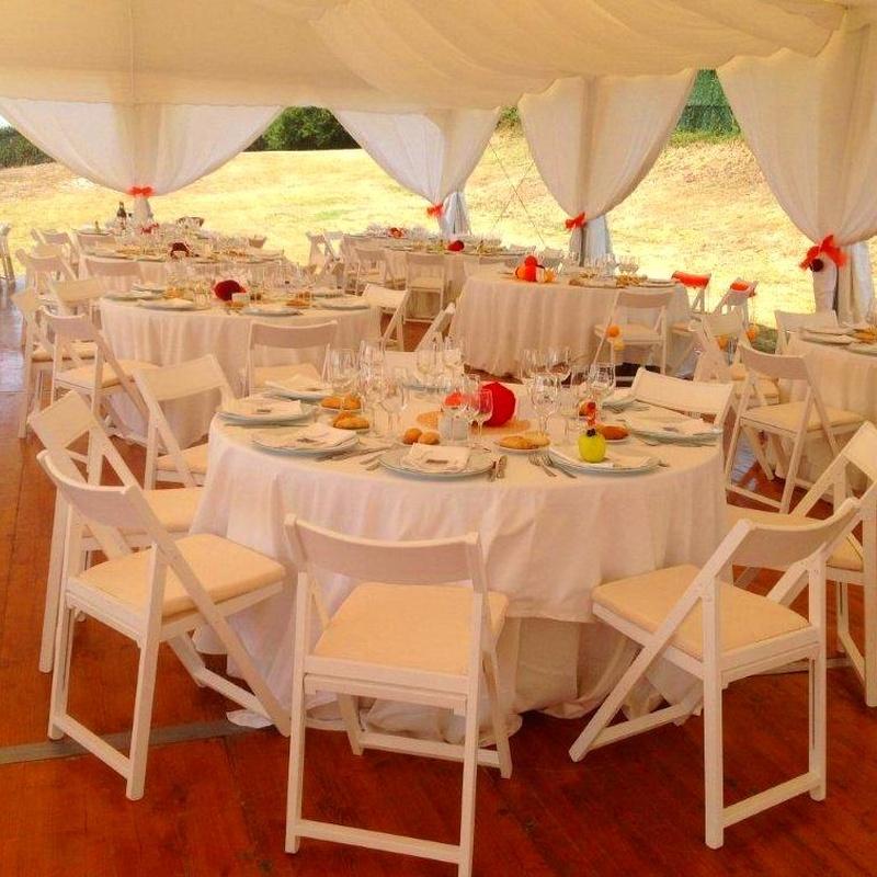 Mesas redondas con mantelería y sillas blancas
