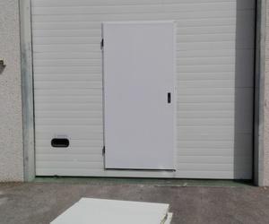 Puerta peatonal de salida de emergencia incorporada en puerta seccional