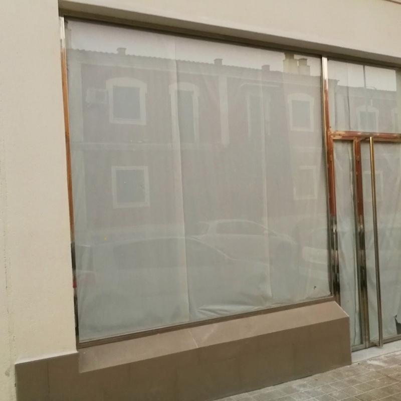 Puerta y escaparate de acero inoxidable y vidrio diseñada y fabricada a medida para local comercial