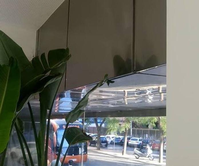Cerramiento de fachada con forros de chapa de acero inoxidable en local comercial