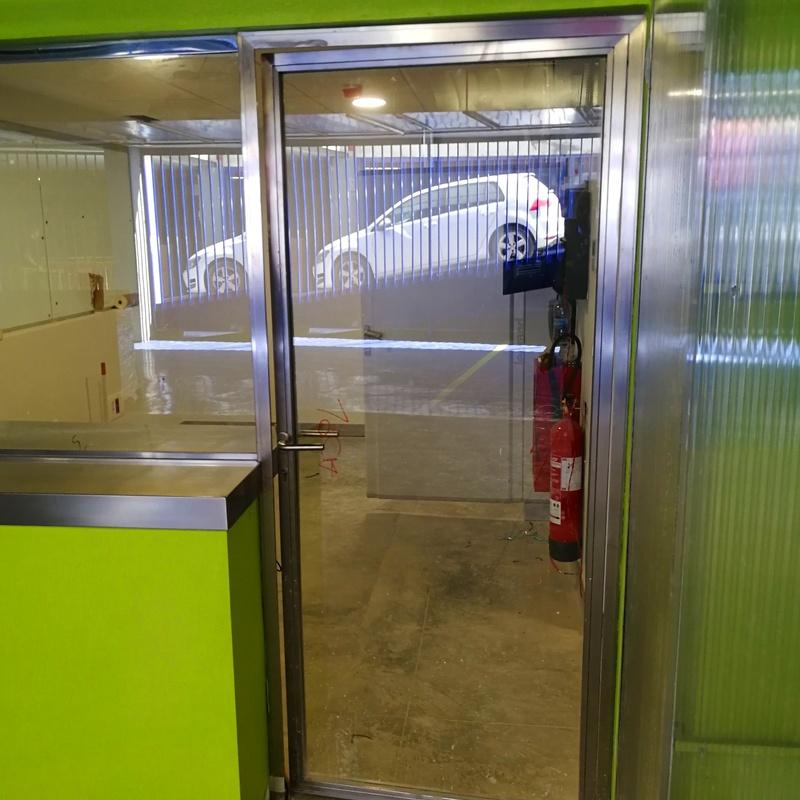Cerramiento de acero inoxidable formado por puerta de acero inoxidable y vidrio, base de acero inoxidable para cristalera de seguridad, y mostrador de acero inoxidable.