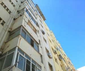 Rehabilitación de fachada con andamio colgado sobre pescantes y cuerdas de seguridad para los operarios.