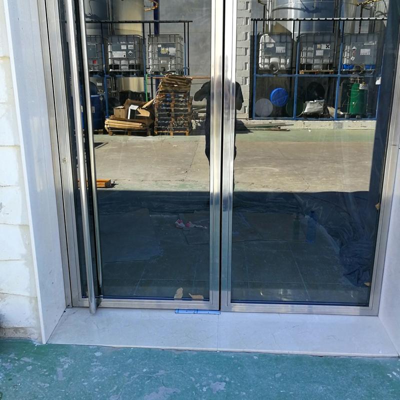 Puerta de acero inoxidable y vidrio diseñada y fabricada a medida para edificio empresarial de zona industrial.