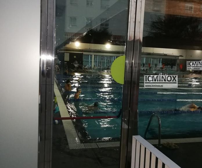 Cerramiento de piscina cubierta. Puerta con sistema antipánico para salida de emergencias fabricado con acero inoxidable de calidad AISI 316