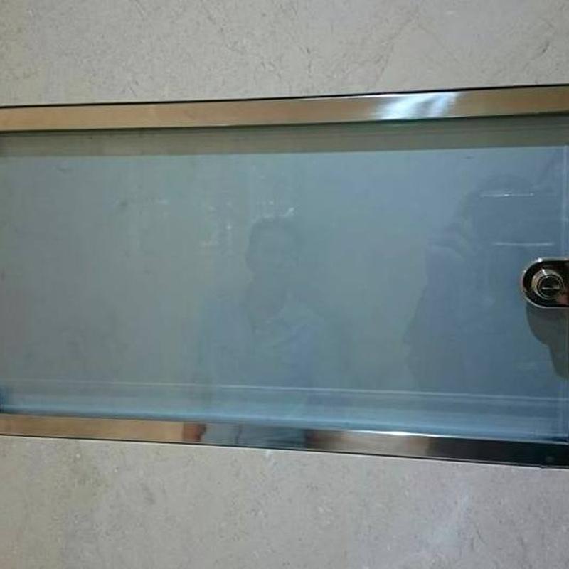 Tablón de anuncios de acero inoxidable y vidrio diseñado y fabricado a medida para comunidad de vecinos.