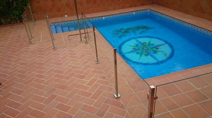 Barandilla de acero inoxidable y vidrio con puerta de acceso a piscina diseñada y fabricada a medida para vivienda particular.