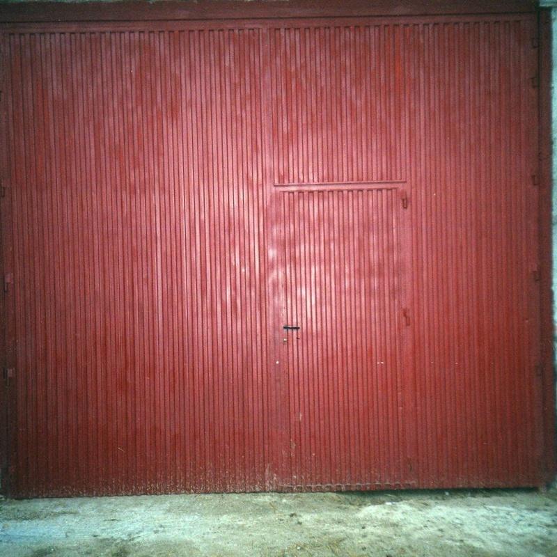 Puerta industrial de dos hojas batientes, con puerta de servicio incorporada.