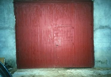 Puerta industrial de dos hojas batientes, con puerta de servicio incorporad