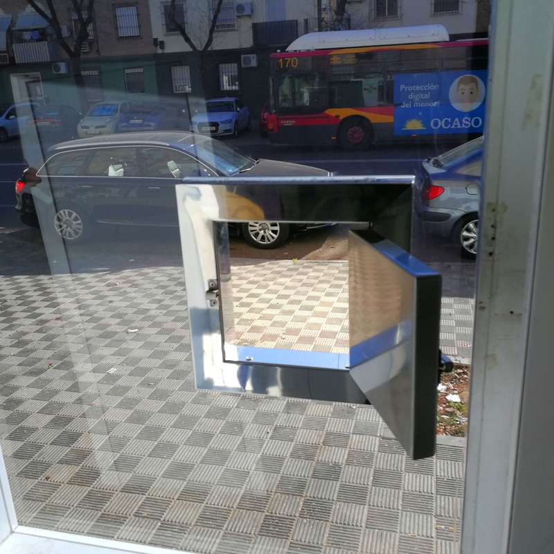 Ventana dispensadora de acero inoxidable diseñada y adaptada a vidrio de seguridad de farmacia 24h.