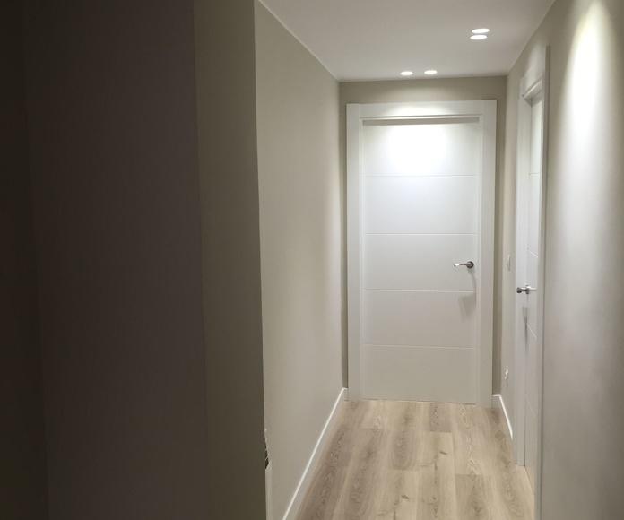 Pasillo con puertas lacadas, eliminacion de gotele, pintura en colores arenas, iluminacion integrada en techo, tarima flotante — en Vitoria.