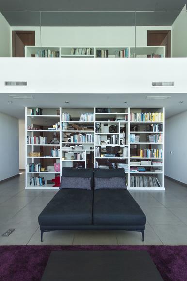Salón a doble altura. La librería acompaña desde el arranque de la escalera. Fotos: http://studio3creativos.es