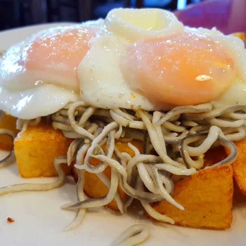 Huevos rotos con gulas al ajillo: Carta de Bar Restaurante Doña Elena