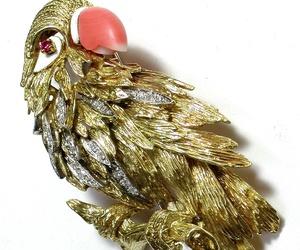 Broche con forma de papagayo en oro bicolor, coral, rubí y esmalte. 1960.