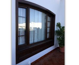 Ventana de PVC de dos hojas con fijo central y barrotillo en el interior y faldón inferior en color nogal