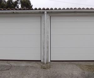 Conjunto de cierre. Puertas seccionales tableadas en RAL 9016. Desbloqueo exterior en puerta derecha.