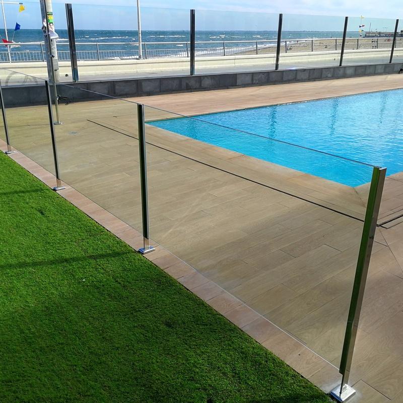 Barandilla de acero inoxidable y vidrio con puerta de acceso a piscina diseñada y fabricada a medida.