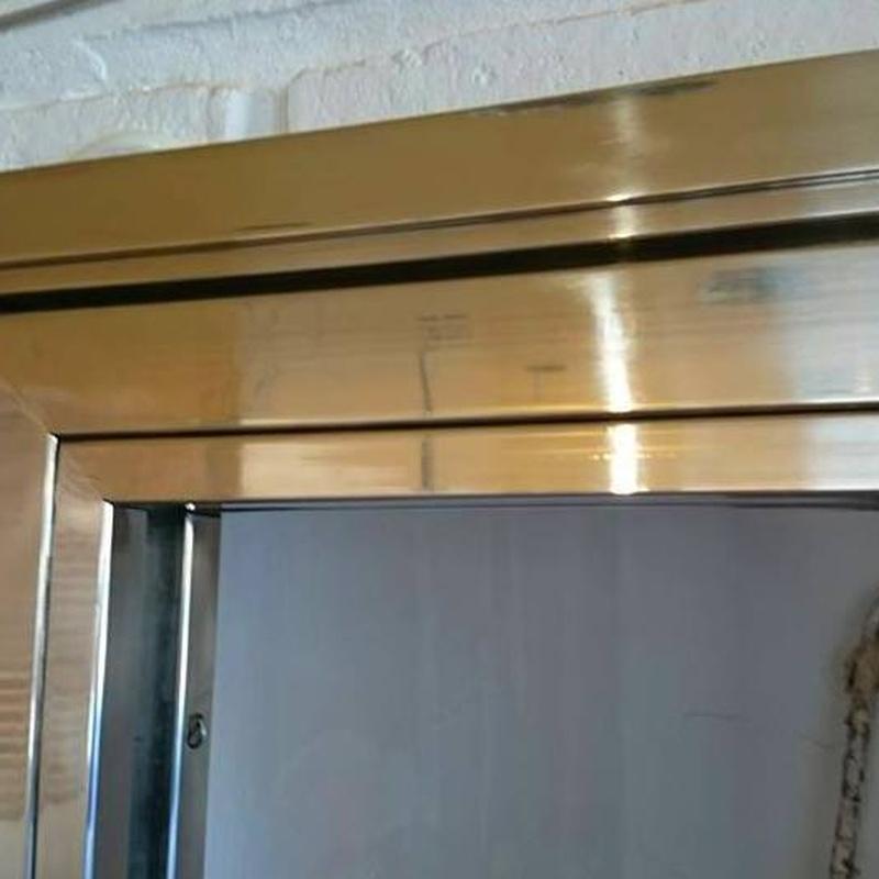 Puerta de acero inoxidable y vidrio fabricada a medida para entrada a bodega.