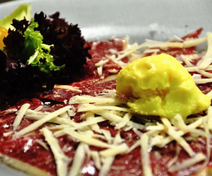 Carpaccio de ternera con su bouquet de brotes, parmesano y helado de aceite de oliva.