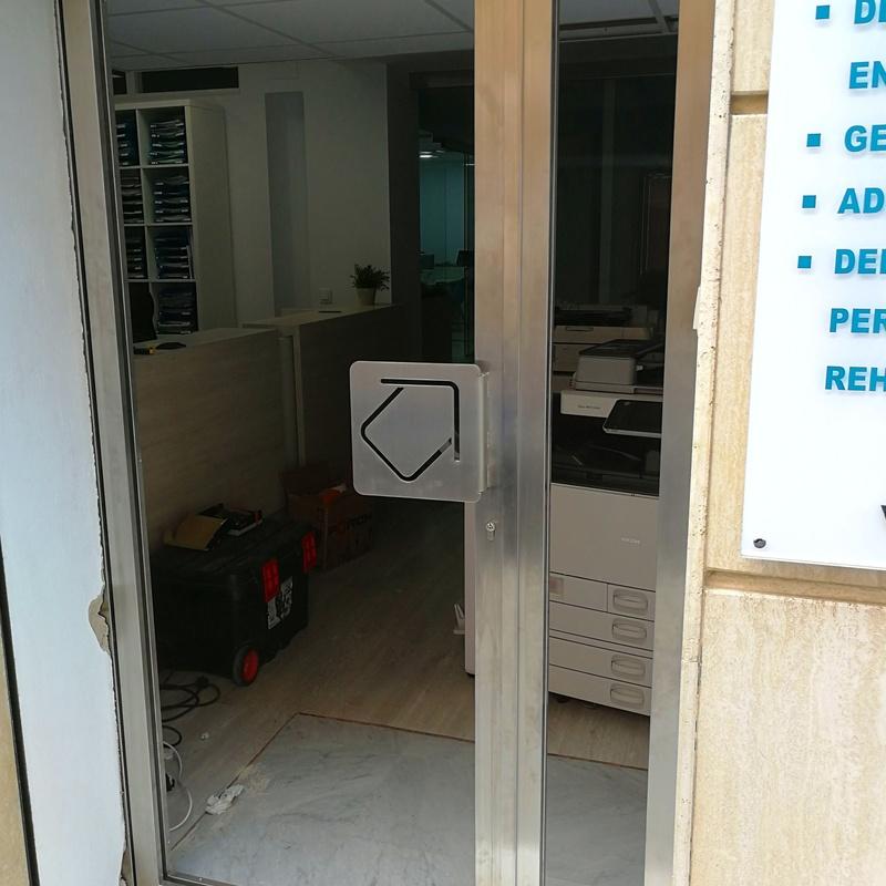 Puerta de acero inoxidable y vidrio con tirador de acero inoxidable personalizado con el logo de la empresa