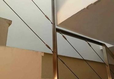Barandilla de acero inoxidable con cables tensores adaptada a la escalera.