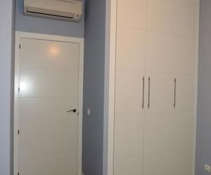 Puerta y armario en el mismo modelo lacados en blanco y tarima Quick Step.