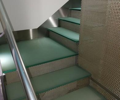 Zócalos de acero inoxidable en escalera de vidrio de hotel en Sevilla.