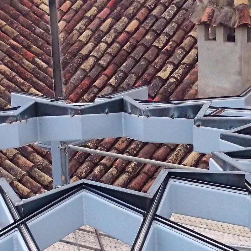 Estructura de techo de acero negro con forma de estrella formando una base totalmente plana para alojar vidrio de la misma forma adaptado a patio andaluz de palacete