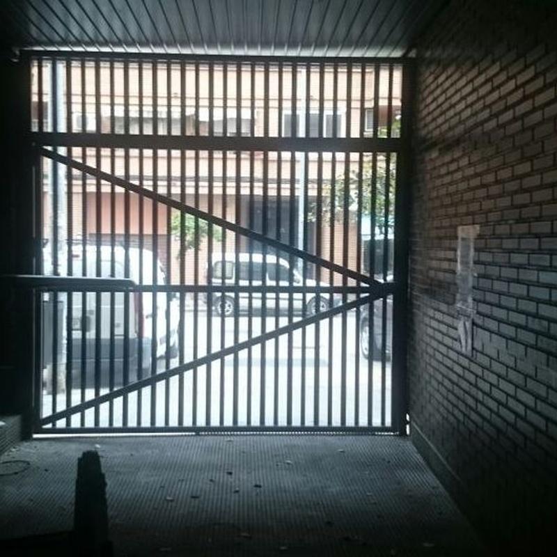 Puerta batiente en garaje comunitario. Lama microperforada y fijo superior de la misma lama. Motor de uso intensivo.