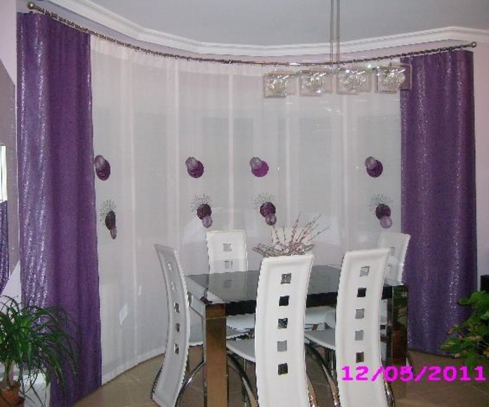 Cortina tipo panel con barra curvada en salon