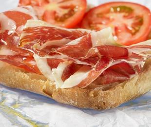 Tostada de pan con jamón, aceite y tomate