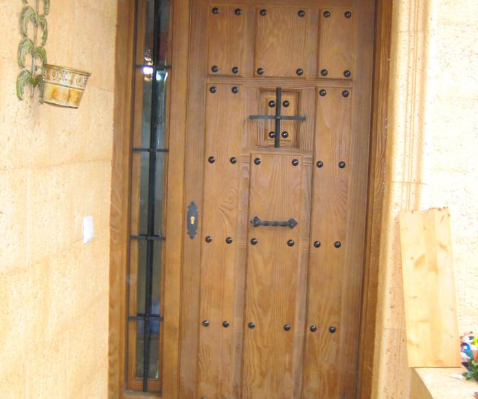 Puerta de entrada de madera maciza teñida en nogal claro y terminación de la beta de madera chorreada