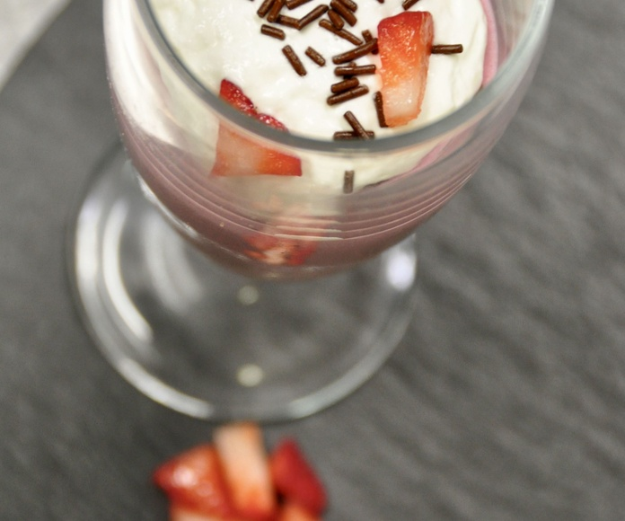 Mousse de frutos rojos, con nata y taquitos de fresa.