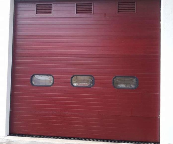 Puerta seccional con ventanas de iluminación y rejillas de ventilación regulable.