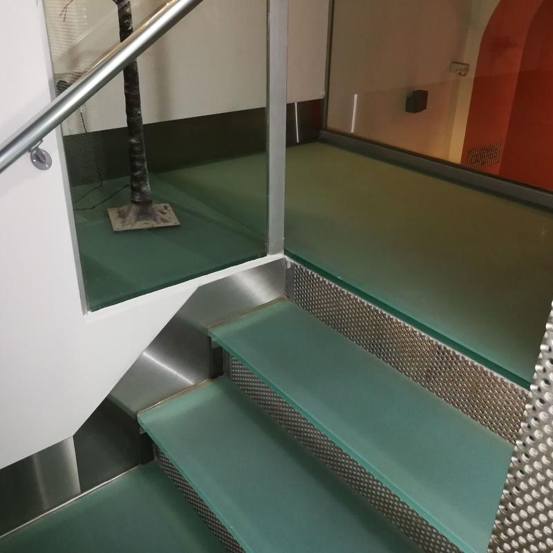 Zócalos de acero inoxidable diseñados y montados a medida para escalera de vidrio de hotel.