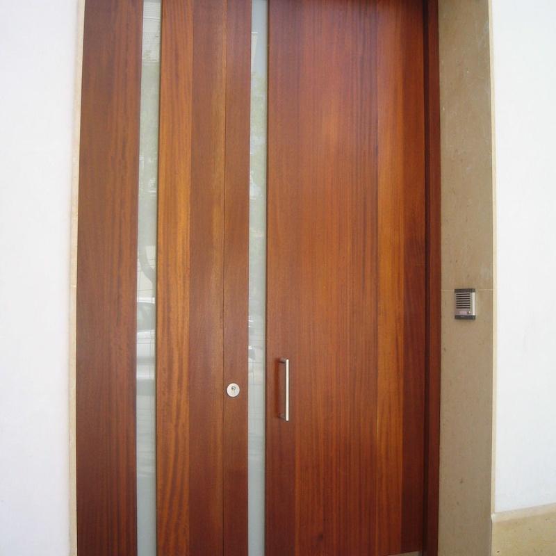 Puerta en madera de Iroko, con zócalo inferior para protección en inox.